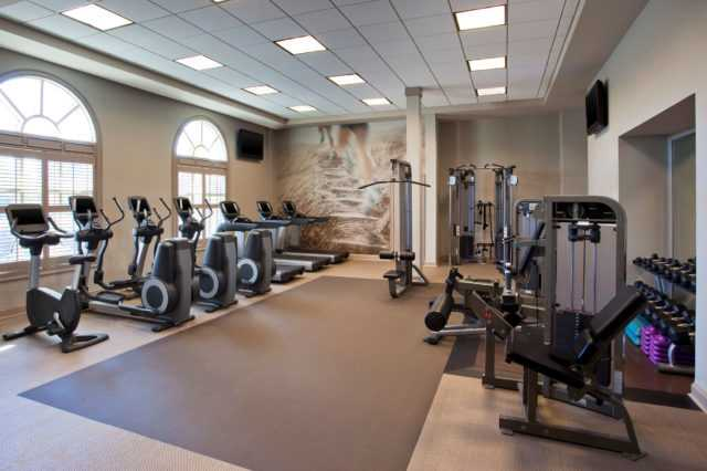 the fitness room equipped with treadmills, weights and bicycles