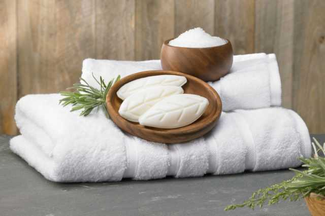 bars of soap held in wooden bowls on top of fresh towels