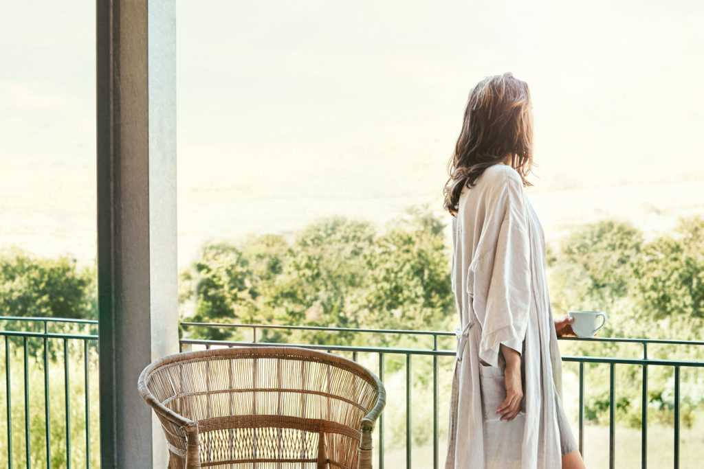 a woman in a robe peacefully looking out on her balcony