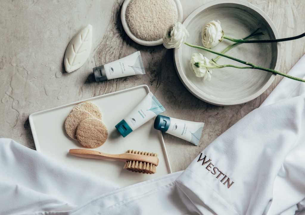 an array of spa creams, brushes and scrubs with fresh flowers