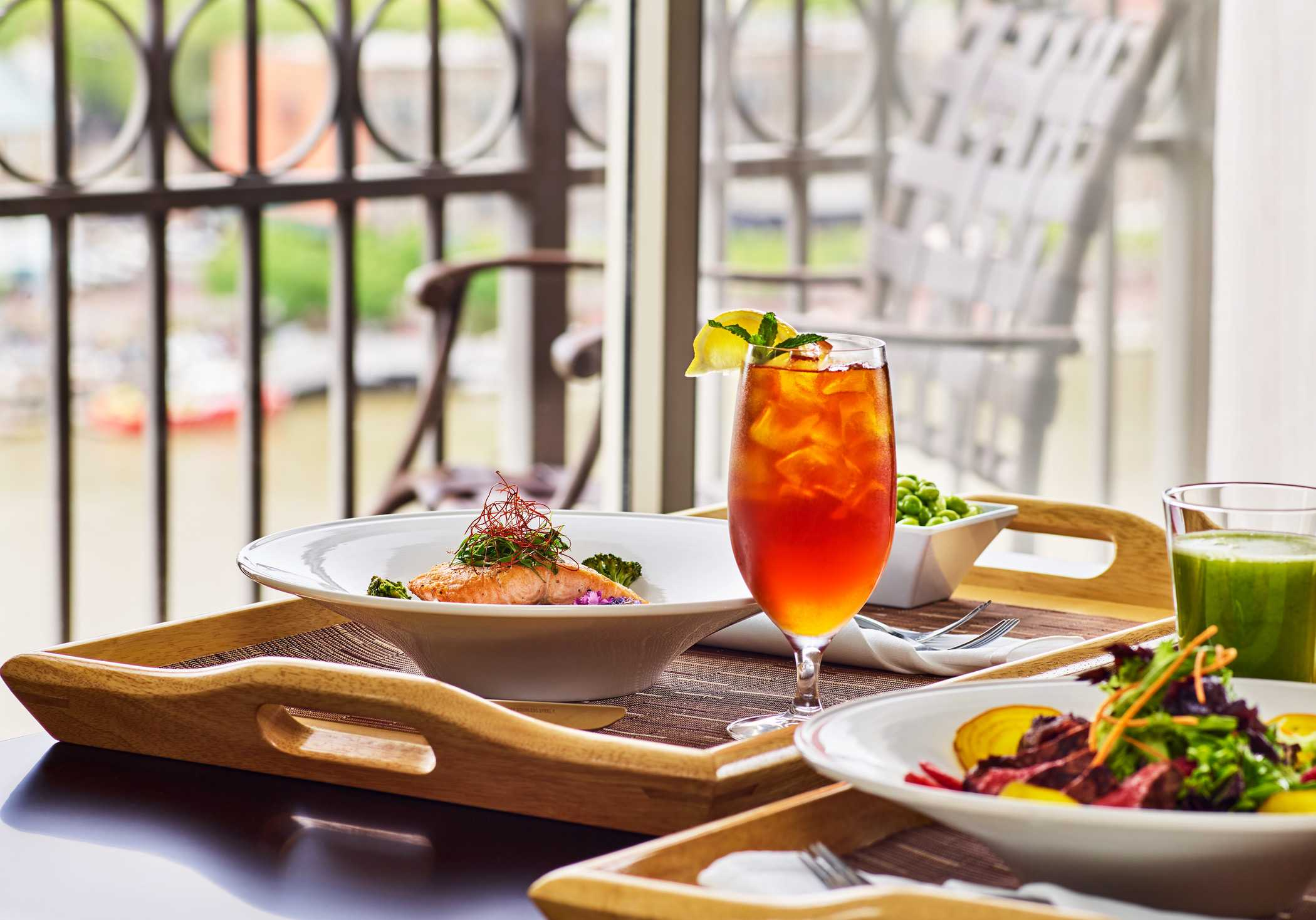 two fresh meals of pasta next to a mixed summer drink on the outdoor patio