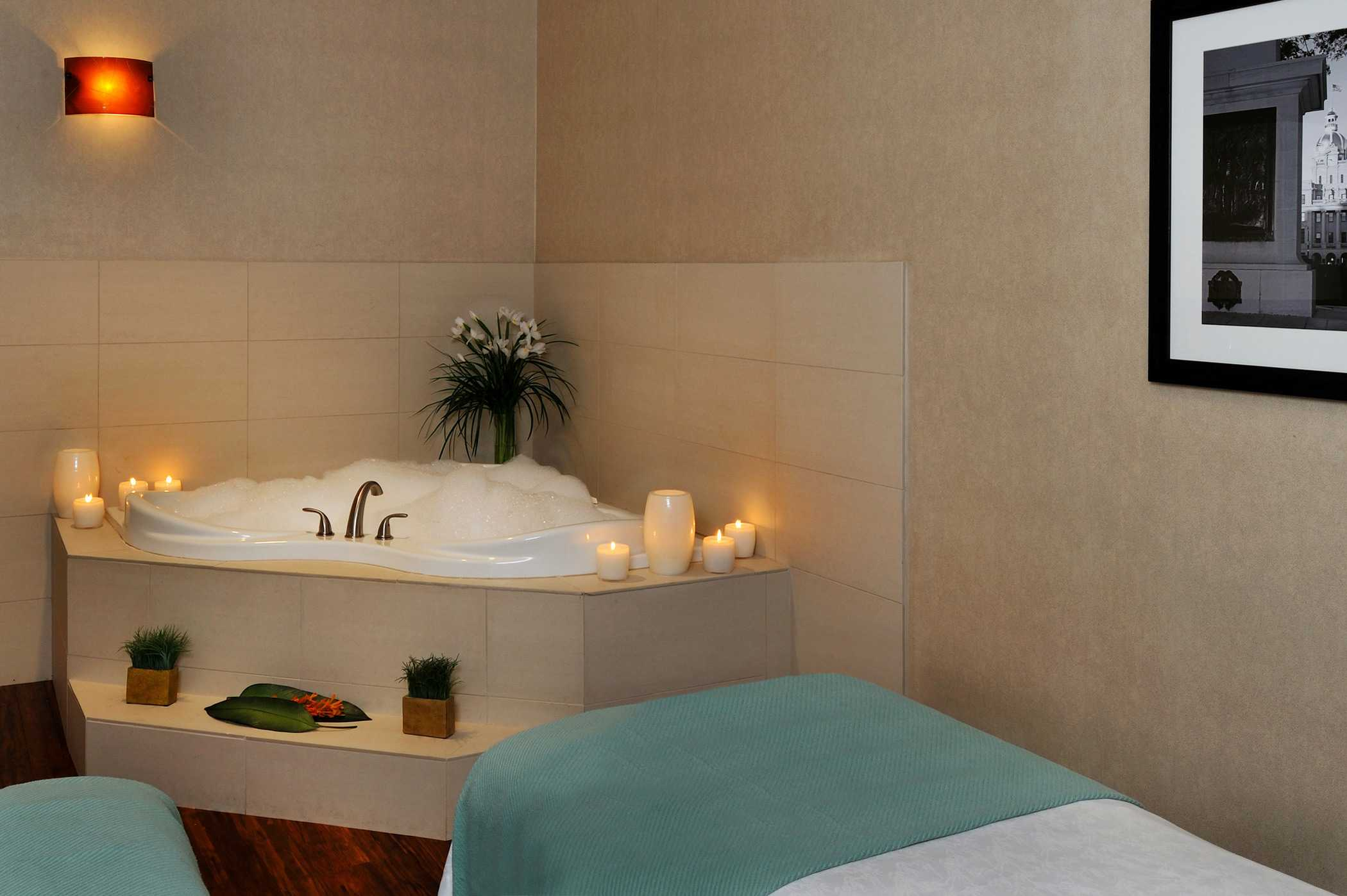 a spa tub prepared with a bubble bath, lit candles and the massage table set