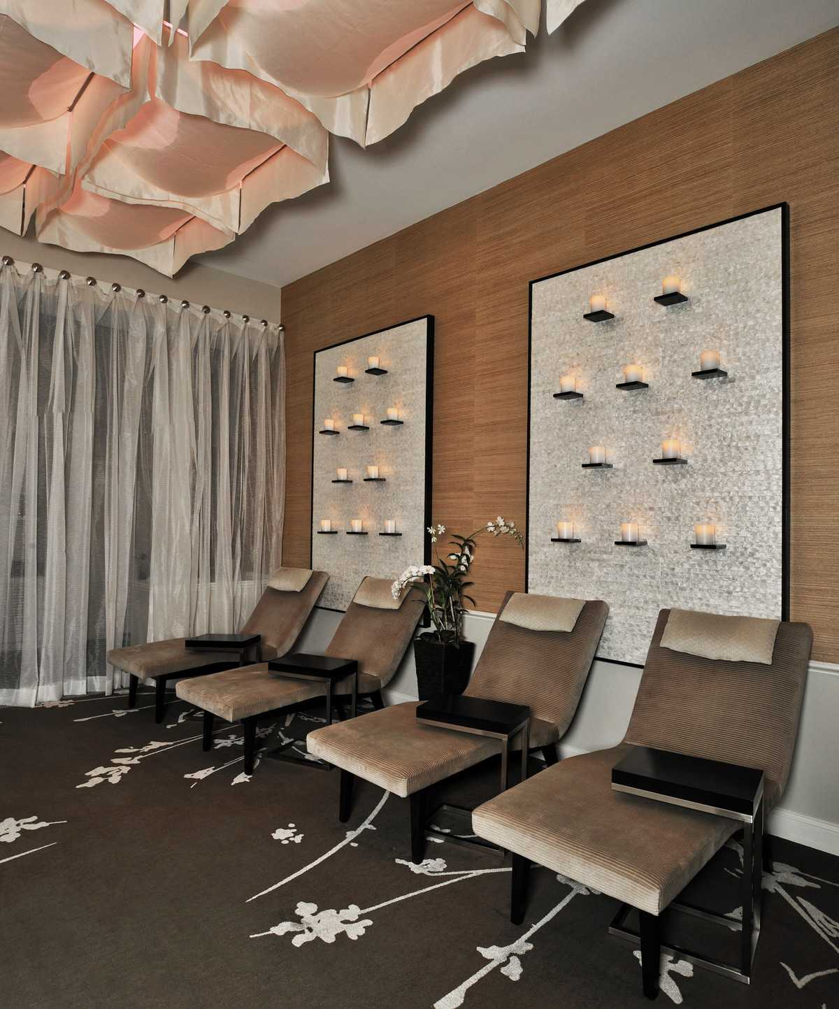 the spa treatment room with an array of four chairs in front of a wall of lit candles